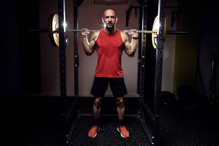 Colpo di uomo atletico culturista muscolare forte che pompa i muscoli con bilanciere su studio scuro.