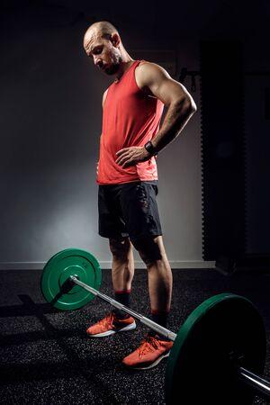 Shot of strong muscular bodybuilder athletic man preparing for training with barbell on dark studio. Zdjęcie Seryjne