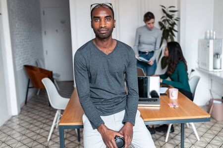 Shot of young afro-american business man entrepreneur looking at camera in the office. In the background, his colleagues working.