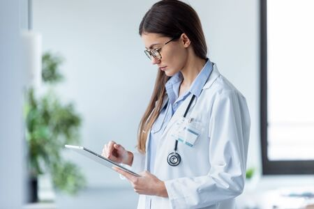 Shot of female doctor using her digital tablet while standing in the consultation. Banco de Imagens