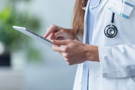 Close-up of female doctor using her digital tablet in the office.