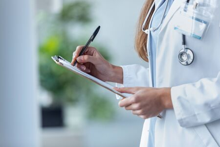 Close-up of a female doctor filling up medical form at clipboard while standing in the consultation.