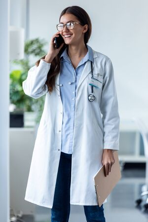 Shot of pretty female doctor talking on mobile phone while standing in medical consultation. Banco de Imagens