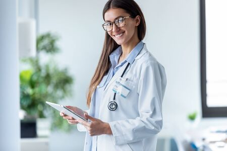 Portrait of pretty young female doctor looking at camera while standing in the office.