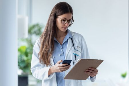 Shot of pretty female doctor using her mobile phone while reviewing medical reports in medical consultation. Banco de Imagens