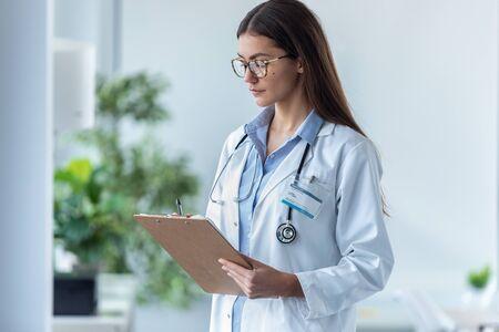 Aufnahme einer konzentrierten Ärztin mit Brille, die medizinische Berichte im Büro im Krankenhaus überprüft.