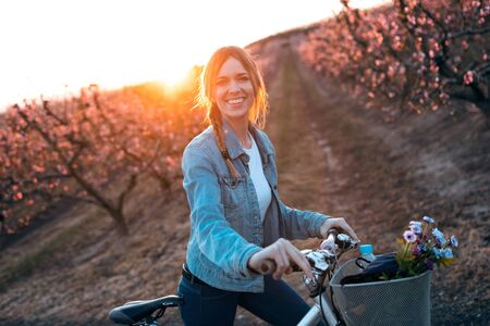 Portrait of pretty young woman with a vintage bike looking at camera in cherry field in springtime. Banco de Imagens