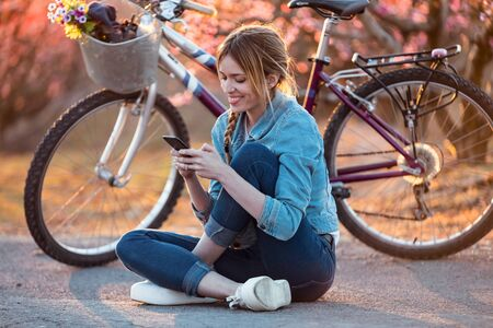 Shot of pretty young woman with a vintage bike using her mobile phone on cherry field in springtime.