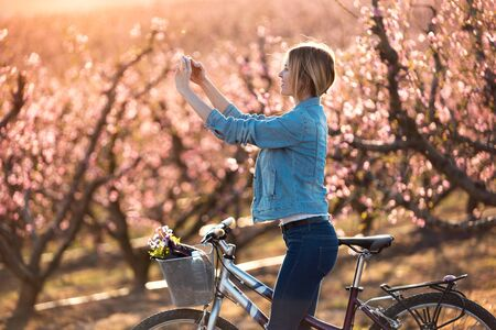 Shot of pretty young woman with a vintage bike taking photographs of cherry blossoms on the field in springtime.