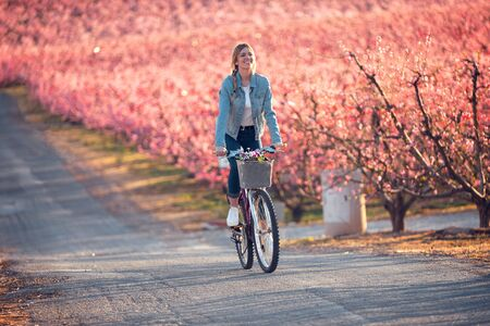 Shot of pretty young woman riding with a bike in cherry field in springtime.