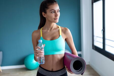 Shot of sporty young woman looking to sideways while holding water before a pilates class on the gym.