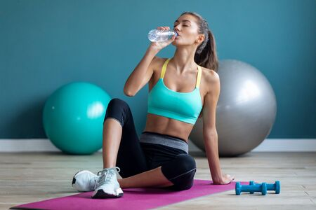 Shot of sporty young woman drinking water while doing pilates exercises on the gym. Banco de Imagens