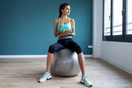 Shot of sporty young woman eating a bowl of muesli while sitting on fitness ball at home.