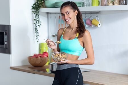 Shot of sporty young woman looking at camera while eating a bowl of muesli in the kitchen at home. Banco de Imagens