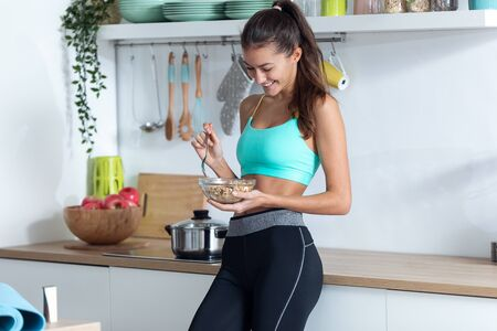Shot of sporty young woman eating a bowl of muesli while standing in the kitchen at home.