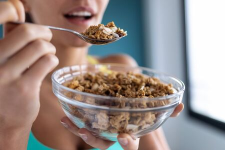 Close-up of sporty young woman eating a bowl of muesli. Health care concept. Banco de Imagens