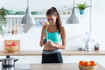 Shot of sporty young woman eating iogurt while standing in the kitchen at home.