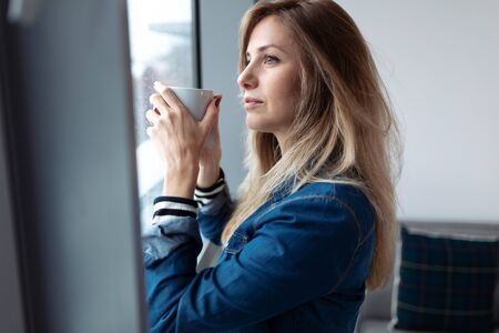 Shot of pretty young woman looking through the window while drinking coffee in the living room at home. Banco de Imagens