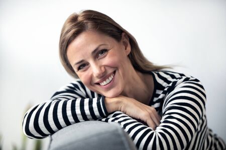 Portrait of smiling young woman looking at camera while sitting on sofa at home.