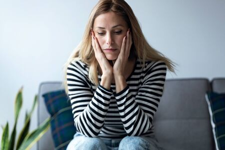 Shot of depressed young woman thinking about her problems while sitting on the sofa at home.
