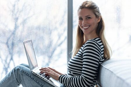 Portrait of pretty young woman looking at camera while using her laptop at home.