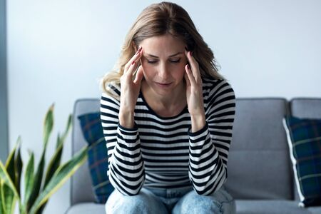 Shot of young woman with headache sitting on the sofa in the living room at home. Banco de Imagens
