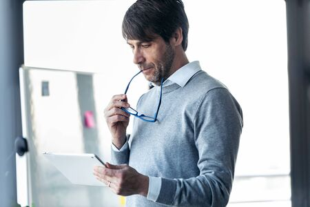 Portrait of elegant businessman working with digital tablet in the office.