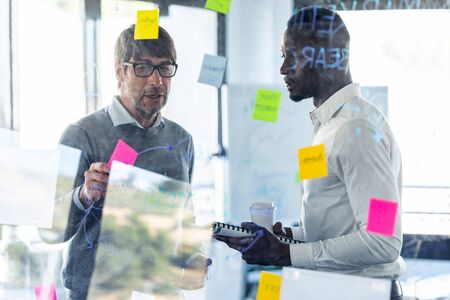 Shot of two handsome business men writing notes at office glass board while discussing together in the coworking space.