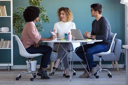 Plan de jeunes gens d'affaires occasionnels travaillant et parlant de leur nouveau projet ensemble au bureau.