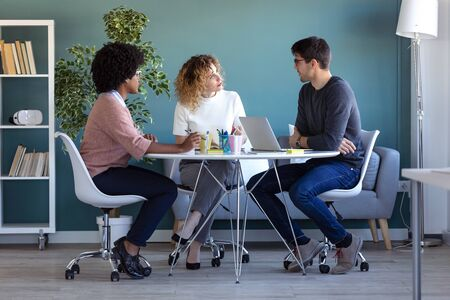 Shot of casual young business people working and talking of they new project together in the office.