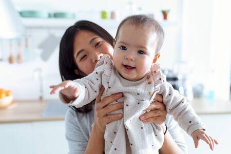Photo d'une jeune mère heureuse avec sa petite fille regardant la caméra dans la cuisine à la maison.