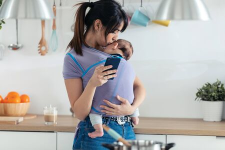 Shot of pretty young mother kissing her little baby in sling while using her mobile phone in the kitchen at home.