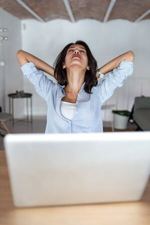 Shot of tired young business woman taking a moment for relax while working with her laptop in the office. Imagens