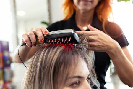 Close-up of hairdresser doing a treatment with ultrasonic and infrared laser comb for hair regrowth in her woman client at the salon.