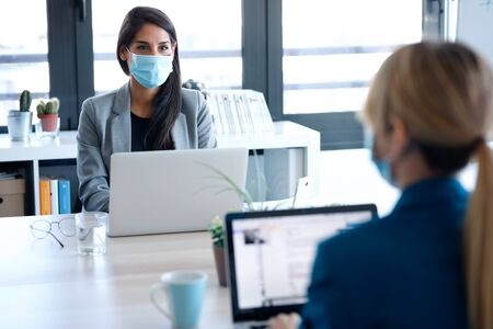 Shot of two business women wearing a hygienic face mask while work with laptops in the coworking space. Social distancing concept.