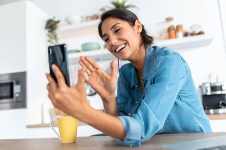 Shot of beautiful young woman making video call with smartphone and waving during morning coffee at home. Foto de archivo