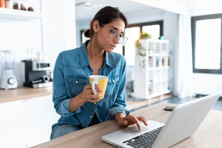 Shot of pretty young woman working with laptop during morning coffee in the kitchen at home.
