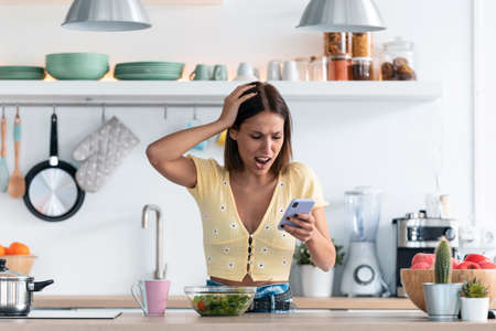 Shot of beautiful young woman using her mobile phone while reciving bad news in the kitchen at home.