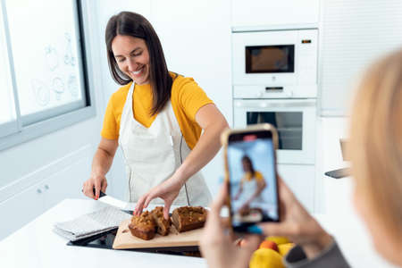 Shot of young woman recording a video and taking photos of her young professional nutritionist while showing handmade carrot cake in the kitchen at home.