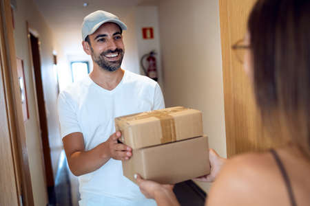Shot of delivery handsome man delivery a few packages to woman at home.