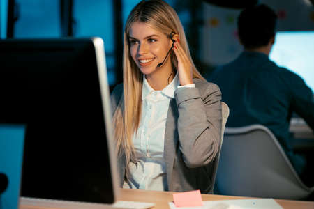 Shot of beautiful smiling young business woman working with computer while talking with earphone sitting in the office.