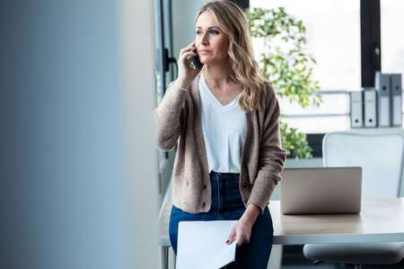 Shot of beautiful mature business woman talking on mobile phone while holding papers looking through the window in the office.