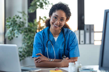 Shot of attractive afro female doctor smiling looking at camera while working with laptop in the consultation. Foto de archivo