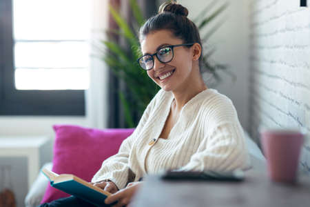 Shot of pretty young woman with eyeglasses reading a book while looking at camera sitting on sofa at home. Foto de archivo