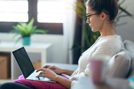 Shot of pretty young woman working with her laptop while sitting on couch at home.