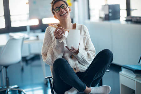 Shot of happy young woman eating noodles with chopsticks while taking a break of work sitting on chair at office. Foto de archivo