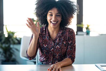 Portrait of beautiful afro young woman waving hand while doing video call looking at camera in the office.