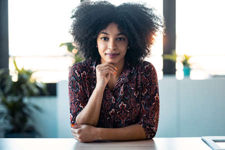 Portrait of beautiful afro young woman explaing something looking at camera while doing video call in the office.