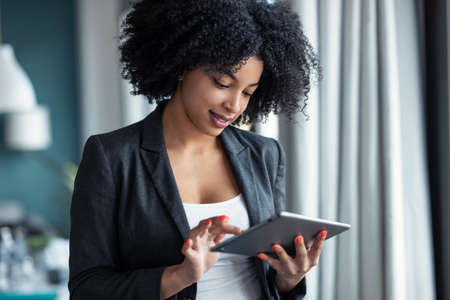 Portrait of smart afro young entrepreneur woman using her digital tablet while standing in the office at home.