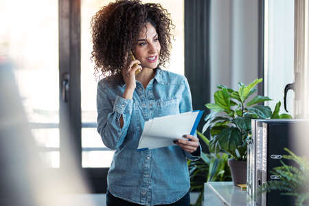 Shot of smart young businesswoman talking with her mobile phone while holding notes looking through the window in the office at home. Foto de archivo